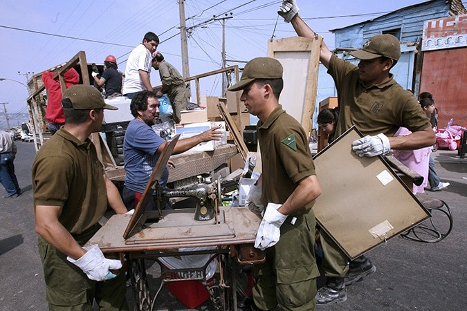 Men hauling furniture from truck