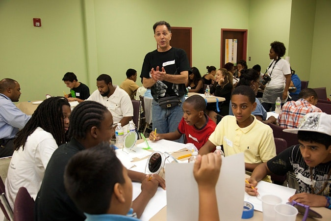 Jay Wolf Schlossberg-Cohen claps at a group of students in a classroomx