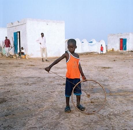 Boy holding rusty bike wheel