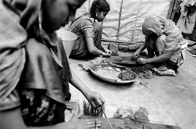 Girls making charcoal sticks