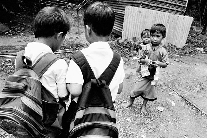Two boys wearing backpacks; two smaller boys stand nearby