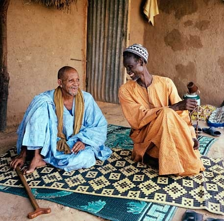 Two men sitting on a rug outdoors