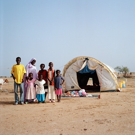 Family in desert standing in front of tent