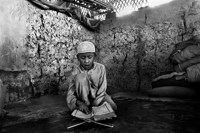 Boy sitting, reading the Qur'an
