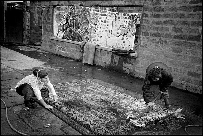 Two women cleaning a rug outdoors