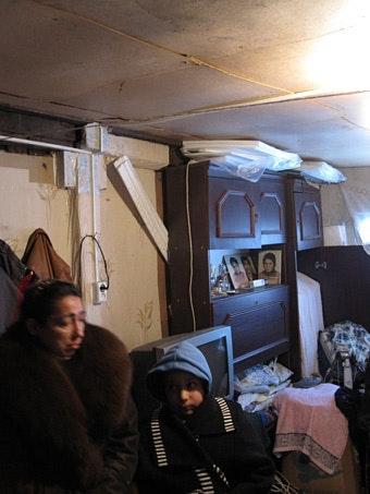 Woman and boy wearing coats inside shack